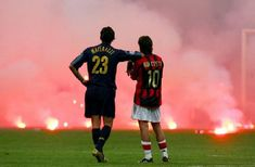 Inter Milan's Marco Materazzi (L) and AC Milan's Manuel Rui Costa waits on the pitch as supporters throw flares onto the pitch during their Champions League quarter-final second leg soccer match at the San Siro Stadium in Milan April 12, 2005. REUTERS/Stefano Rellandini