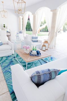 White outdoor living room with outdoor drapery, white sofas, and a colorful rug. Outdoor Living Rooms, Coastal Living Rooms, Outdoor Spaces, Living Room Decor, Living Spaces, Outdoor Seating, Indoor Outdoor, Tropical Decor, Coastal Decor