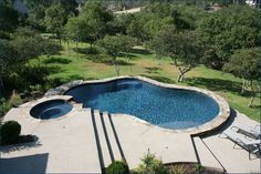 Freeform pool with Spa set on a hill- also prefer the dark color to the light botton pools
