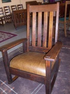 Arts and Crafts: Stickley rocking chair. Tall back with slats, wide flat arms. Dealer claims chair is signed.