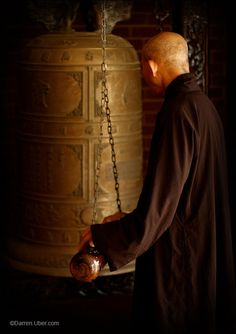 monk ringing the temple bell