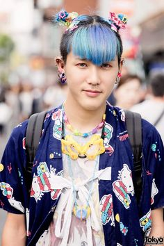 """June 2015: Kanata's hair is styled in blue-green double buns.He has a Hello Kitty jacket over a Park Harajuku manga-print t-shirt, shorts, and purple Reebok sneakers with mismatched socks. Accessories include goggles, a Casio Baby-G watch, candy bracelets, lots of earrings and ear spikes, a giant """"United Sports Club"""" backpack, and kawaii hair accessories from 6%DOKIDOKI."""