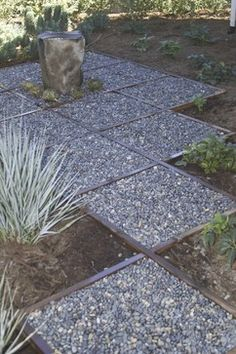The wood edging in this shot is used with gravel to break up a section of landscape. When using wood like this, make sure to treat the wood against rot and use an edging tool to dig a shallow trench for the pieces you install.