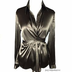 Gorgeous stretch satin wrap blouse with tie back Pretty stretch satin blouse with flattering wrap style that ties in the back. Zip closure, fold down collar. Excellent condition w/ exception of one of the string loops is missing, but the wrap style of this isn't vital to have it. Please read my 'about me' listing for my closet policies before any inquiries/offers. For preloved items, respectful/reasonable offered 'considered'. Keep in mind PoshMark takes 20% commission from each buyers…