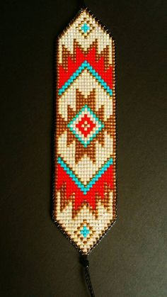 Bright and bold beaded loom bracelet handmade to order. Inspired by Native American designs with a modern edge. Using gold Japanese beads, surrounded by bright turquoise, red and pearlescent design. Edged with black silky nylon cord and finished with Loom Bracelet Patterns, Bead Loom Bracelets, Bead Loom Patterns, Beaded Jewelry Patterns, Peyote Patterns, Beading Patterns, Bead Loom Designs, Beadwork Designs, Native Beadwork