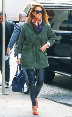 Jessica alba wears an olive green parka, a scarf, skinny leather leggings, orange pumps, top-handle bag, and sunglasses