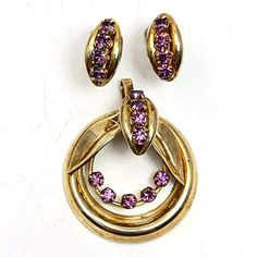 "Art Deco Era Rhinestone Pendant Earring Set Purple Amethyst Art Deco era purple amethyst rhinestone pendant earring set with gold tone plating. Floral design set has screwback style earrings. Brand: unbranded Material: glass Approximate Size: Pendant 1 3/8"" x 1 5/8"" Condition: very good, pre-owned Your purchase will be shipped in an attractive jewelry gift box #FeedCondUsed #FeedAgegroupAdult #earrings #FeedCustomproduct #FeedColorPurpleGold #FacebookFeed"