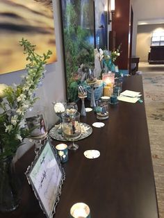 Used vases with beach sand and shells with a picture of family and deceased for a table of memories.  Found Candles in tiffany blue color (her favorite color).  Various beachy decor as well