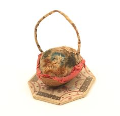 An unusual pincushion in the form of a basket, modelled from a walnut shell and mounted on a pain