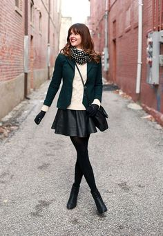 For an edgy meets flirty work look, wear a leather skater skirt with black tights, a sweater and blazer.
