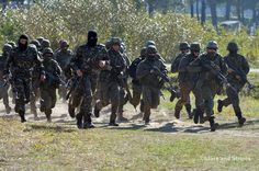 Soldiers from various nations hustle back to the starting point after taking part in cordon-and-search training at Exercise Rapid Trident near Yavoriv, Ukraine, Friday, Sept. 19, 2014. (Michael Abrams/Stars and Stripes)