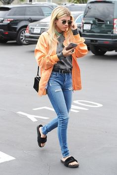 Sofia Richie looks effortlessly cool in her Fenty x Puma furry slides with an orange jacket and jeans