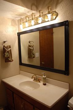 cheap interesting way to frame our a standard construction Bathroom mirror - not permanent so it's good for renters