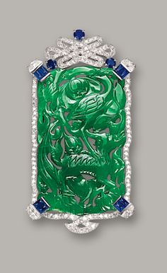 JADEITE, DIAMOND AND SAPPHIRE BROOCH, CARTIER, CIRCA 1950 The jadeite plaque of translucent intense emerald green colour, carved with a crane and mythical beast, symbolising longevity, surmounted by a Chinese eternity knot set with circular-cut diamonds, highlighted by half moon-shaped diamonds, circular-cut sapphires and sugarloaf cabochon sapphires, mounted in 18 karat white gold, signed and numbered 50-27720.