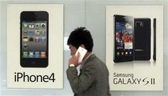 FILE - In this Nov. 22, 2013 file photo, a man walks past banners advertising smartphones by Samsung and Apple at a mobile phone shop in Seoul, South Korea. (AP Photo/Yonhap, Han Sang-kyun, File) KOREA OUT ▼28Apr2014AP|Closing arguments delayed in Apple-Samsung trial http://bigstory.ap.org/article/closing-arguments-set-apple-samsung-trial