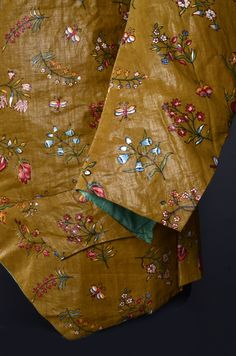 Detail sleeve, long-sleeved at-home waistcoat, ca. 1780-1790. Glazed cotton, block printed with a design of naturalistic flower sprays on light brown ground, fabric-covered buttons; quilted green silk taffeta lining.