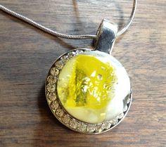 Luminoso: é um colar delicado, com um pingente de metal circundado de cristais, e uma gema de vidro artesanal ao centro.