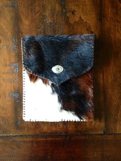 A hair on hide iPad case, lined in chocolate brown suede with a turquoise and silver concho closure. gowestdesigns.us