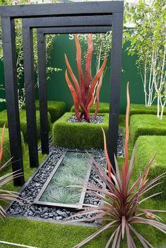 bojes, guijarros grises y chimenea decorativa en el jardín Zen contemporáneo