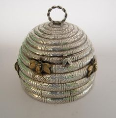 An electroplated biscuit box modelled as a honey skep, with brass and enamel bees.