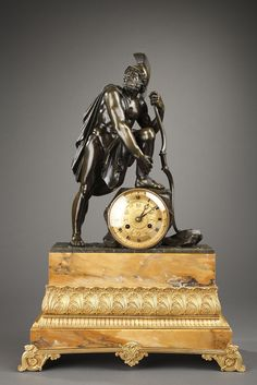 An important mantel clock representing a Romain warrior in bronze with dark green patination.  Faithful to the classic tradition, the sculptor represented a nude warrior wearing the Romain helmet and a drapery covering his right shoulder and one of his legs only. The gilt bronze concave dial with Roman numerals for hours, chiselled with stylized palmette and lily flowers. The clock rests on a naturalist bronze base, a high Siena marble plinth.  Circa.1820