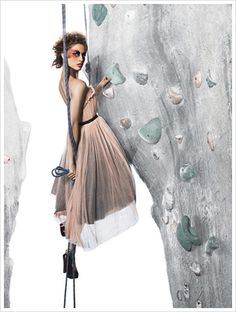 America's Next Top Model wearing expensive fashions up high on a gym's climbing wall.