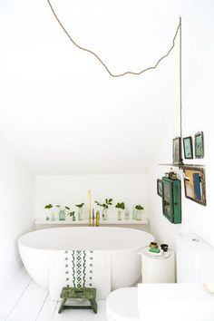 Bathroom with a freestanding tub, an exposed bulb light, and green accents