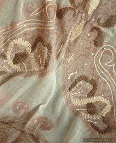Elegante ed ampio scialle da sera in calda e morbida lana merino dai colori delicati, proveniente dalla città di Puna, in India. Lo scialle ha fondo color avorio su cui spiccano ampie parti decorate con complessi disegni della tradizione Kashmira realizzati in colori morbidi come l'écru e il beige, ravvivati e sottolineati da ricami in filato di lana spessa e da applicazioni di paillettes e perline color avorio. I ricami richiamano la forma di delicati ventagli e movimentano la ricca ...