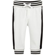 Baby boys black and white tracksuit trousers from Dolce and Gabbana. Made in cotton jersey with a towelling textured inside, these warm trousers have a black stripe on the side of each leg. They have stitched pocket details on the front and back and an elasticated, ribbed jersey waistband with drawstring ties. The ankles are ribbed to match. A designer label is attached on the back.