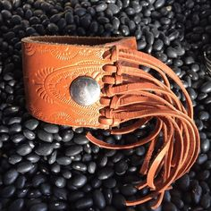 The Texas Toast fringe leather cuff features an intricate stamped pattern. This leather cuff is trimmed in toast brown dear lace. Cuffs are made by Rowdy Ann out of up cycled leather belts. Each one i
