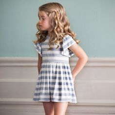 Beautifully soft, blue and white striped cotton jersey dress byPatachou, with a wide neckline and loose sleeves that drape over the shoulders. The full, gathered skirt falls from the gold-piped waistband and the back has a concealed zip, secured with a monogrammed, mother of pearl button and loop fastening. Can be dressed up with gold accessories or worn with sandals for a more casual look.