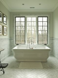 The master bath of this French Country style home is furnished with a traditional stand-alone air tub, with floor tile made of Carrera marble. (via Cynthia Lynn Photography)