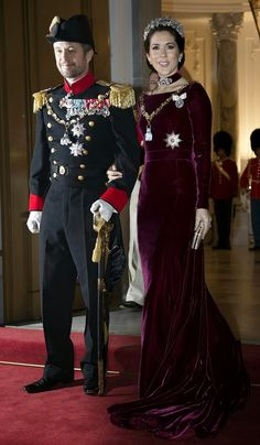 Crown Princess Mary and Crown Prince Frederik. The Crown Princess was wearing a Burgundy prom dress in silk velvet as they arrives for the traditional 2014 gala dinner at the Amalienborg Palace