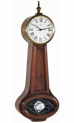 Hermle reproduction of the American Banjo wall clock in a classic Cherry finish. Bookmatched diagonal grain cherry waist panel with a fretted glass pendulum window. Brass Dial is hinged and opens from the right. Speckled white antique style dial with Roman numerals. Quartz battery controlled German Chiming movement with dual chimes with both Westminster and Bim Bam swinging polished brass pendulum. Size: H 22 W 10 D 4 1/8 inches