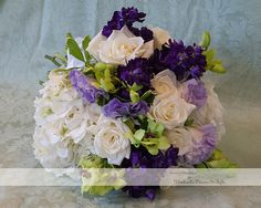 Purple stock, lavender lisianthus, green cymbidium orchids arranged with white roses and hydrangeas