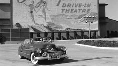 "Two women in a vintage convertible drive past a sign advertising Hollywood's Olympic Drive-In Theatre in <a href=""  http://www.travelchannel.com/destinations/los-angeles/photos/things-to-do-in-la"">Los Angeles, CA</a>, in 1951."