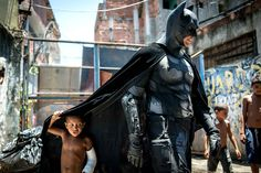 Children play around a man disguised as Batman at the Favela do Metro slum, area just near the Maracana stadium, in Rio de Janeiro, Brazil, on January 9, 2014. Families living in this shantytown within a stone's throw of Rio's mythical Maracana stadium refuse to have their homes demolished as part of a project to renovate the district before the FIFA World Cup circus pitches camp in June.  AFP PHOTO / YASUYOSHI CHIBA