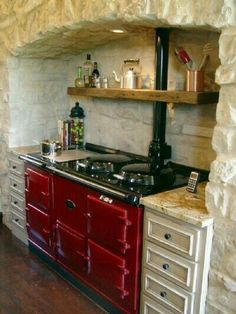 A red Aga stove would be in my dream kitchen. Love the 'hearthlike' feel of the way this is set into stone. Aga Kitchen, Farmhouse Kitchen Cabinets, Cottage Kitchens, Country Kitchen, Home Kitchens, Kitchen Dining, Kitchen Decor, Kitchen Ideas, Kitchen Chairs