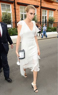 Cara Delevingne in a white dress with flutter sleeves and strappy heels