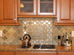 This kitchen features light wood cabinets, marble countertops and a classic backsplash with a simple diamond border. The alternating diamond tiles present a bold look with the addition of a miniature frame.