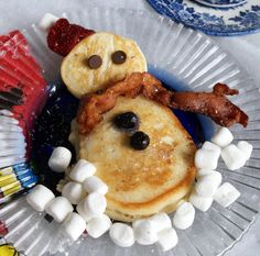 Snowman breakfast ~ to pancakes add bacon scarf, marshmallow snow, blueberry buttons, chocolate chip eyes, strawberry hat.