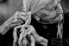 Old woman braiding her silver hair