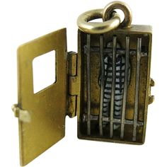 Rare antique 14K yellow gold mechanical charm, Convict's Yale, in the form of a jail cell containing a prisoner enameled in traditional