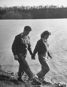 Ohio State Univ. student Bud Shively and his date Vivian DeMaria walking along shore of river.