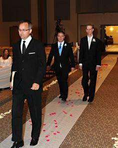 Officiant, groom, and best man walking down the aisle