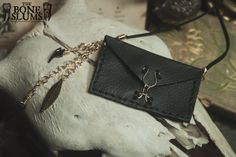 This beautiful envelope style medicine pouch has entirely gold hardware and features a handmade closure. The scrap leather it is made from is a soft black, hand sewn together with artificial black sinew. From its left corner three chains fall, at the end of each lies one of the following: a hand ...