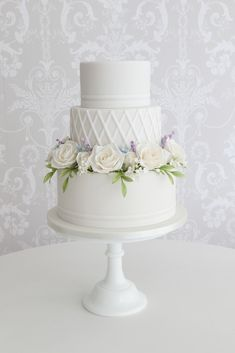 Three tier traditional wedding cake with beautiful floral details and a delicate iced pattern gives this a modern twist. Image Zoe Clark Cakes wedding cakes 19 Wedding Cake Ideas you will love ~ KISS THE BRIDE MAGAZINE Fondant Wedding Cakes, Wedding Cake Roses, Floral Wedding Cakes, Amazing Wedding Cakes, White Wedding Cakes, Wedding Cakes With Flowers, Elegant Wedding Cakes, Wedding Cake Designs, Wedding Cupcakes