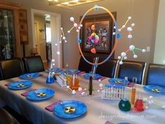 Mad Scientist party is simple to create with colored water filled glass containers, styrofoam molecules and homemade slime.