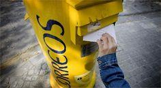 Una persona echa una carta a un buzón de Correos, empresa que el año pasado registró en toda España un total de 4.631 millones de envíos postales.