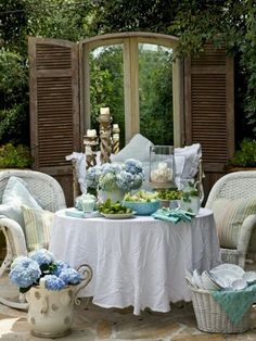 Love this shabby chic patio. Blue hydrangeas and accessories.